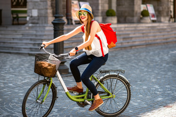 Young female tourist with backpack and hat riding a bicycle in the old city center of Ljubljana in Slovenia