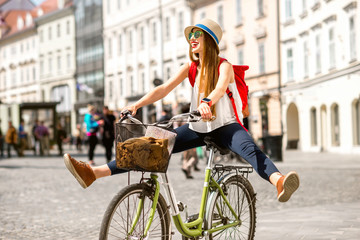 Young female tourist with backpack and hat having fun riding a bicycle in the old city center of Ljubljana in Slovenia