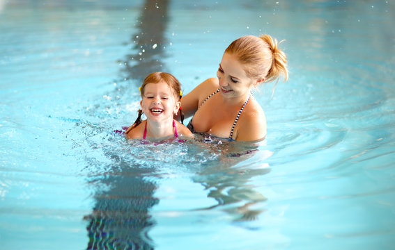 mother teaching child daughter swimming pool