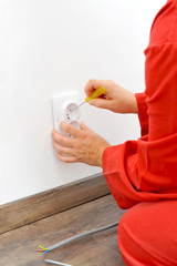 Close up of electrician hands fixing socket