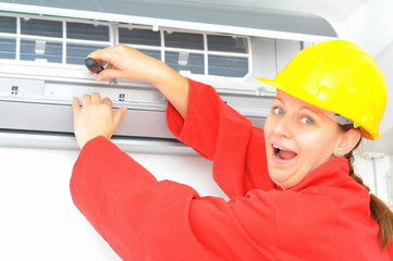 Woman worker adjusting air conditioner system