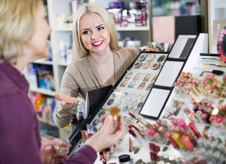 Positive  woman customer chooses cosmetics
