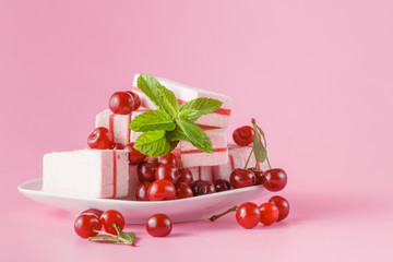 fresh cherry on sweets on plate on pink
