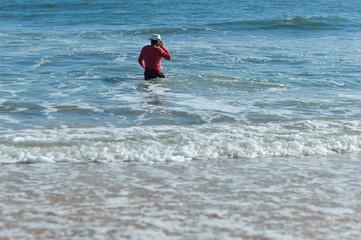 Handsome active man using smartphone, seaside background. Back side view