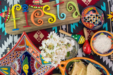 Mexican fiesta table decoration with  colorful painted letters, bright pottery.