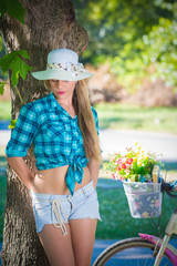 Portrait of female model posing by leaning against the tree in a park. Bicycle with basket full of flowers in the background. Summer, lifestyle and fashion concepts. Space for copy.