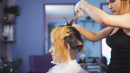 A radical change of hair color. Attractive blonde woman in a beauty salon