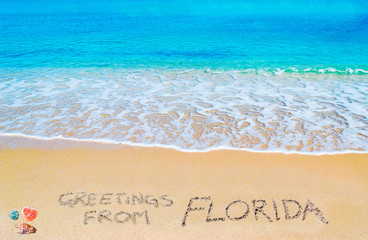 greetings from FLorida written on a tropical beach