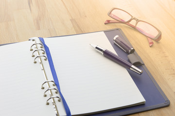 Businessman write a short note on opened notebook on wooden background with pen, glasses. warm tone.
