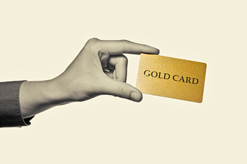 """Black and white toned photo a hand with  """"gold card""""  on a isolated background"""