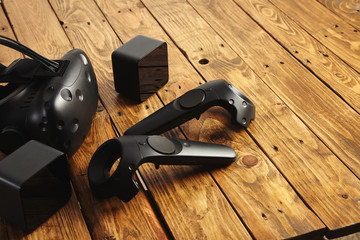 VR equipment set presented on rustic wooden table: goggles, scanners, two remote controllers Next generation video gaming console