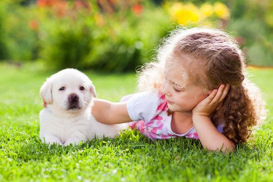 Little girl with a labrador puppy, outdoor summer