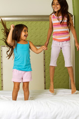 Portrait of playful siblings jumping on a bed