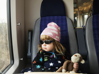 Girl wearing sunglasses and cap sitting in train