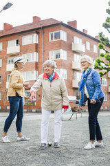 Senior women playing boule on field by street against buildings