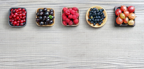 Set of different berries on wooden background. Copy space for your text. Top view, high resolution product.