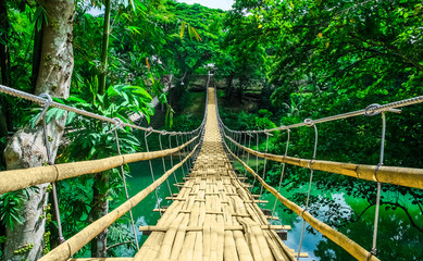 Zelfklevend Fotobehang Brug Bamboo hanging bridge over river in tropical forest