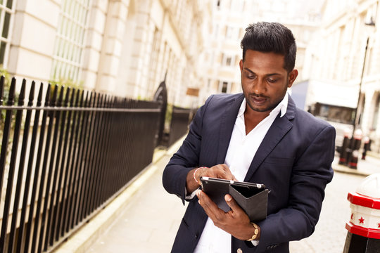 oung man using an tablet in the street