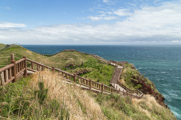 View of a coastal walkway next to the Songaksan Mountain on Jeju Island in South Korea.