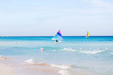 Tourists float on a sailing catamaran. Active sports leisure. Varadero sandy beach at sunny day. Cuba.