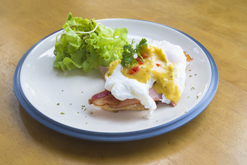 Eggs Benedict- toasted English muffins, Bacon, poached eggs, and delicious buttery hollandaise sauce