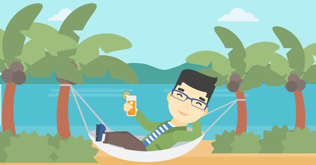 Man chilling in hammock with cocktail.