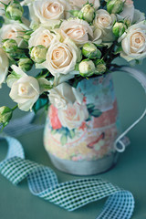 Beautiful fresh beige roses flowers in a vase .