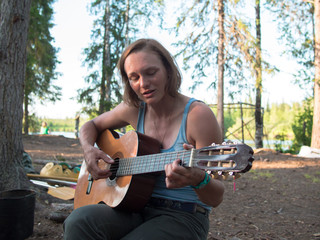 Young woman playing guitar on forest background