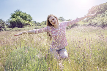 romantic beautiful teenage girl with arms stretched like flying