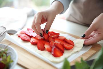 Female hands cooking strawberry dessert in kitchen