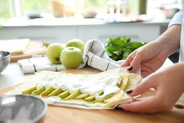 Female hands cooking apple dessert in kitchen