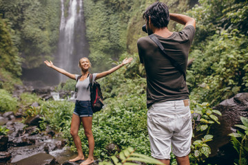Photographer taking photos of a woman near waterfall