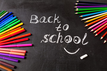 """Back to school background with colorful felt tip pens and title """"Back to school"""" written by white chalk on the black school chalkboard"""