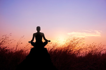 Woman yoga and meditation silhouette on nature sunset background