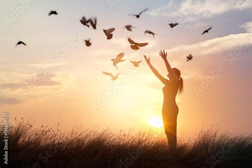 Leinwandbilder Woman praying and free birds enjoying nature on sunset background
