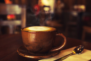 cup of hot coffee on table in cafe with morning light - vintage and dark color tone styles