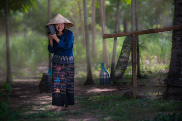 Asian woman in traditional dress listen radio outdoor,countryside Thailand.