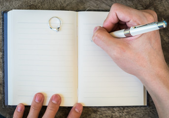 Hand writing white pen notebook with diamond ring in memory