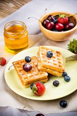 Waffles with berries on wooden background