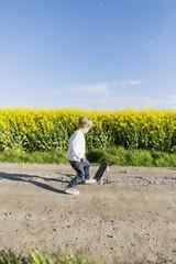 Boy skateboarding on dirt road at oilseed rape field