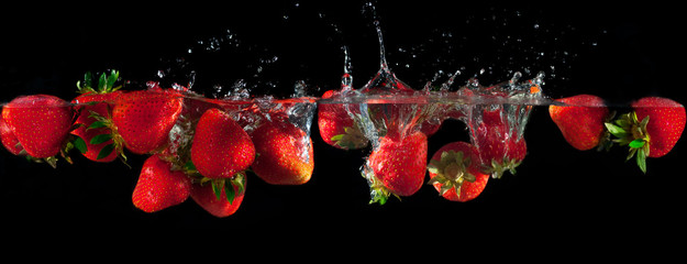 Strawberries splashing into water on a black background