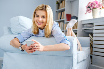 Portrait of smiling blond female lying on a couch.