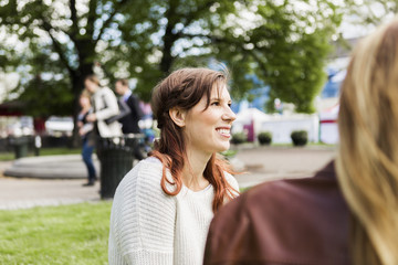 Young smiling woman looking away while sitting by friend at park