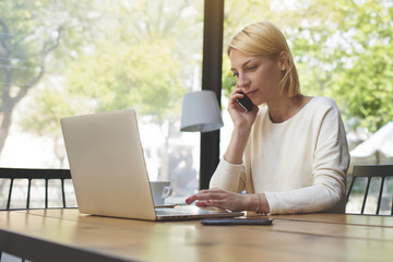 Businesswoman is calling with cell telephone and working on laptop computer