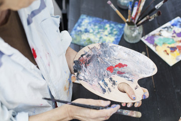 Midsection of senior woman using palette and paintbrush