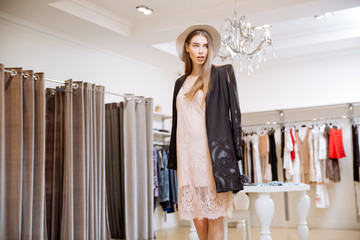 Attractive young woman in hat standing in clothing shop