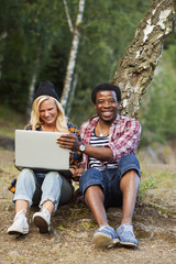 Portrait of happy man sitting with woman using laptop in forest
