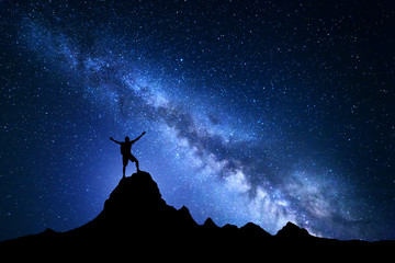 Landscape with Milky Way. Blue night sky with stars and silhouette of a happy climber with backpack and raised up arms on the top of mountain. High Rocks. Travel background with silhouette of a man.