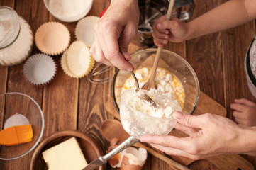 Woman hands, ingredients and devices for preparation muffin on a wooden background. House pastries. Food concept. Flour, eggs, butter, mix for pastries.