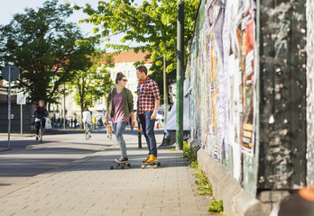 Full length of happy couple skateboarding on sidewalk